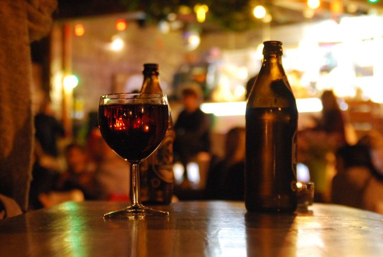 Wineglass with bottle on table at cafe