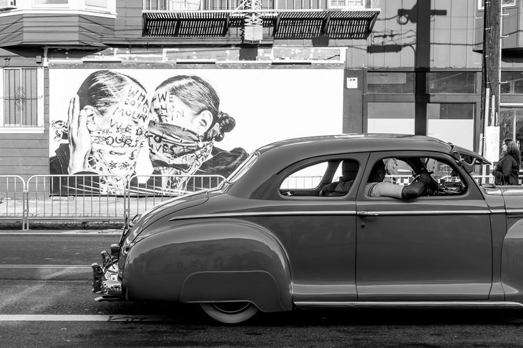 Side view of man riding vintage car on street