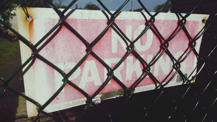 Close-up of no parking sign behind chainlink fence