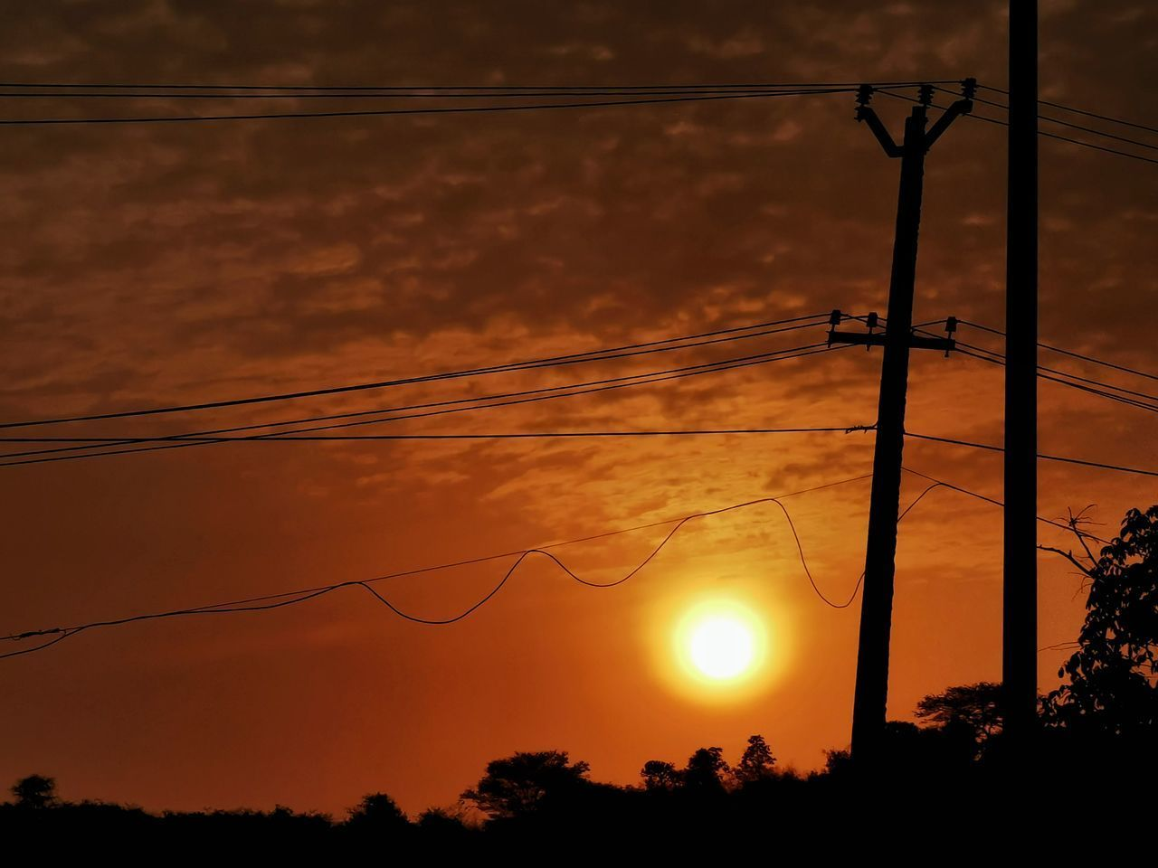 LOW ANGLE VIEW OF SILHOUETTE ELECTRICITY PYLON DURING SUNSET