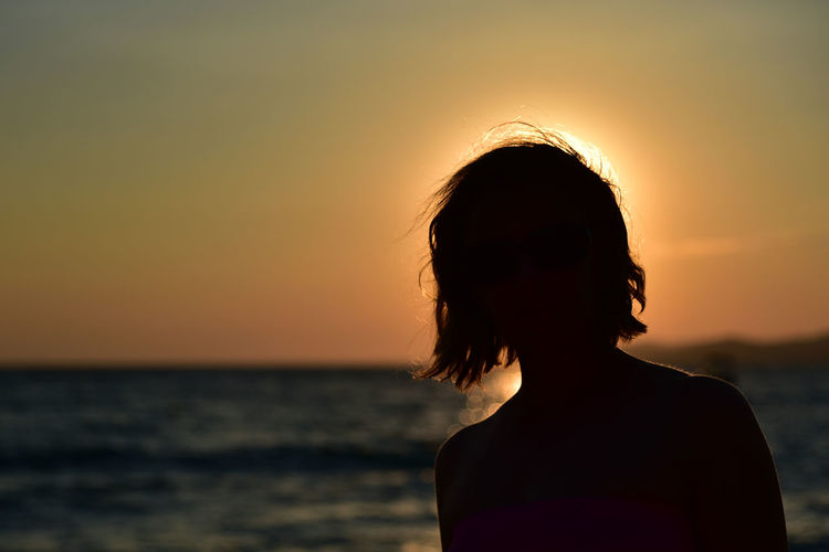 Silhouette woman looking at sea during sunset