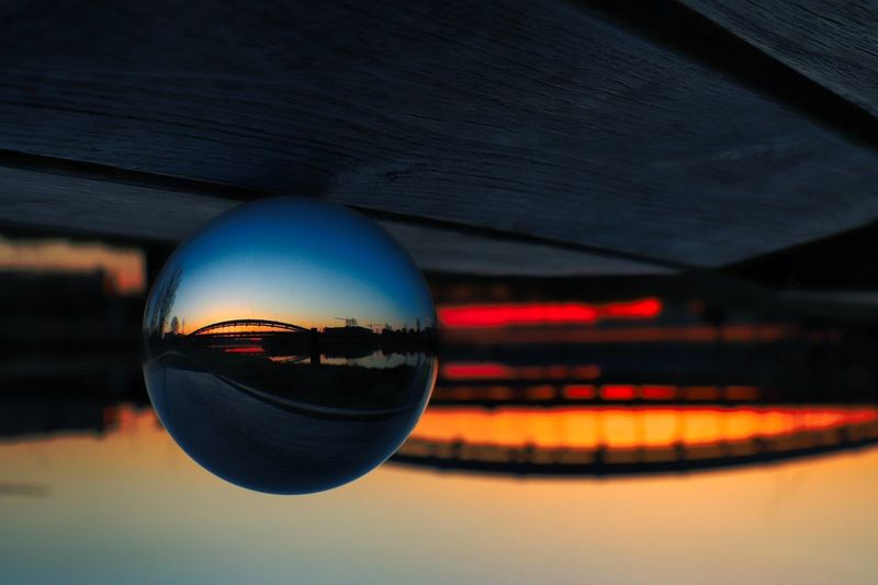 Close-up of crystal ball on glass against sunset sky