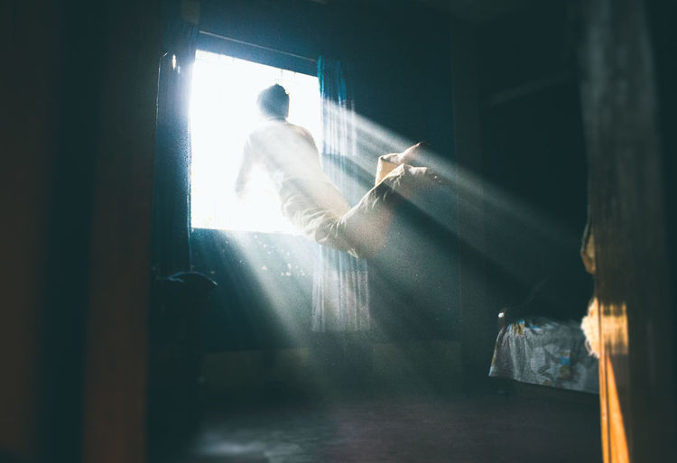Man in mid-air by brightly lit window at home