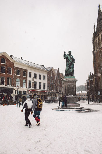 Statue on snow covered city against sky