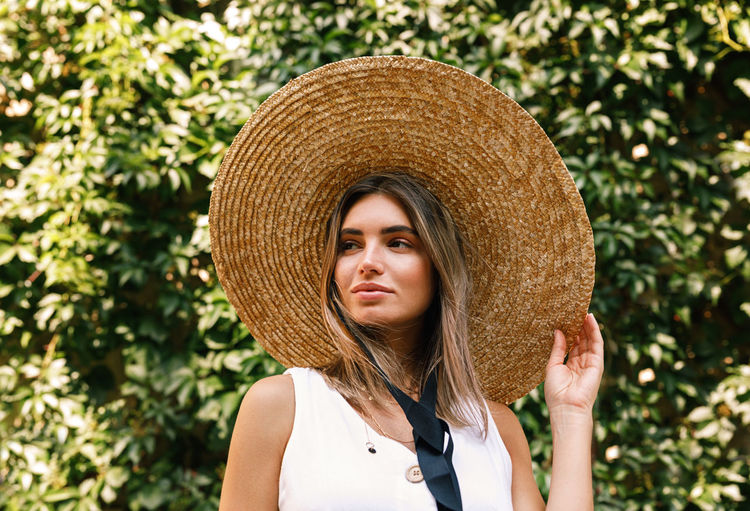 Beautiful woman wearing hat standing against plants in park