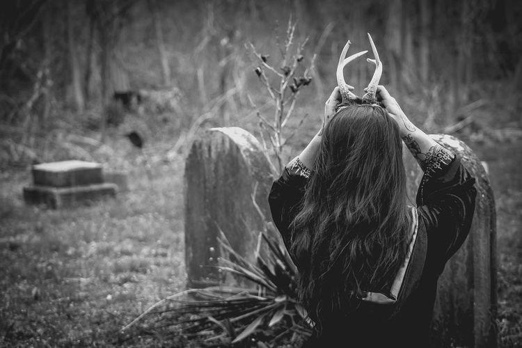 Rear View Of Woman Holding Antlers On Head Over Field At Graveyard