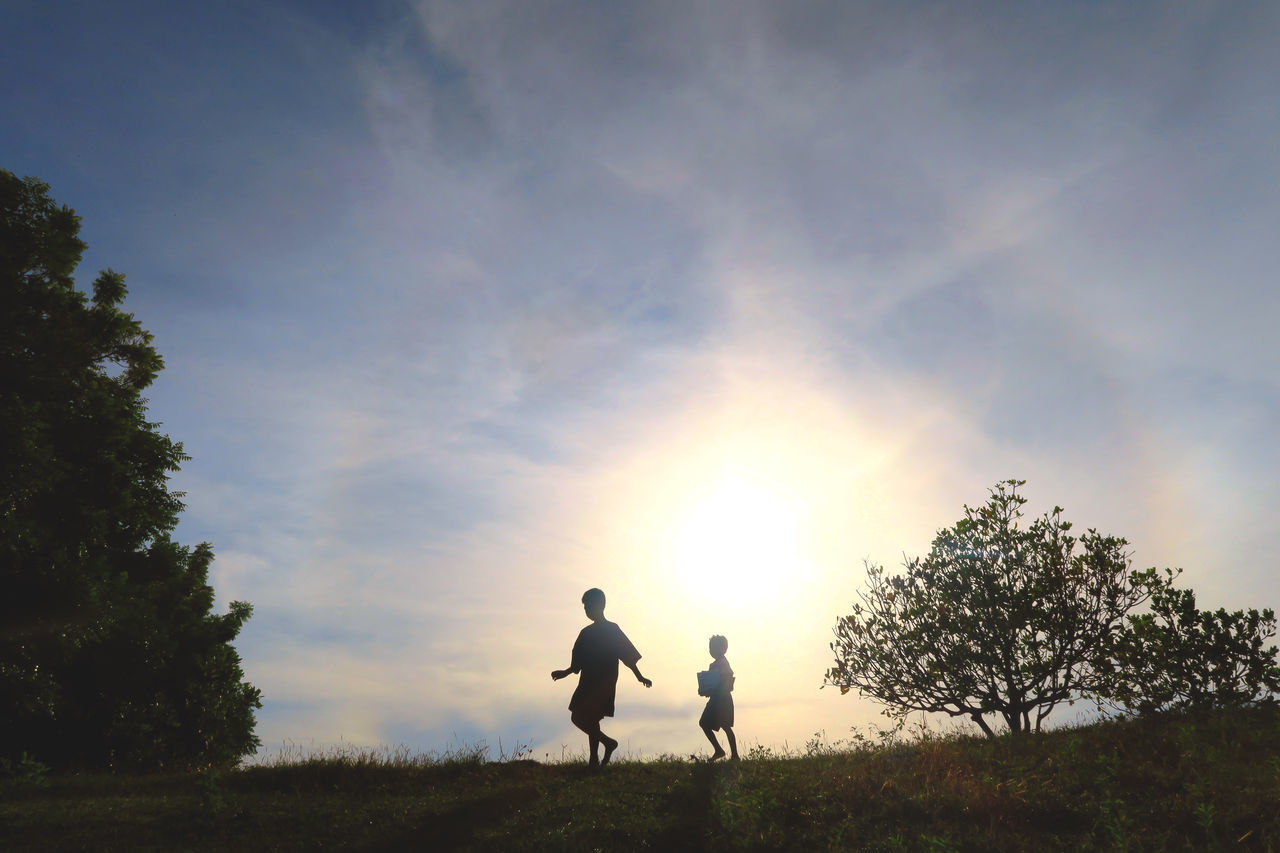 real people, togetherness, sunset, men, sky, leisure activity, nature, father, family with one child, bonding, walking, silhouette, lifestyles, tree, family, field, son, cloud - sky, boys, beauty in nature, outdoors, love, standing, low angle view, childhood, friendship, grass, full length, scenics, growth, day, adult, people