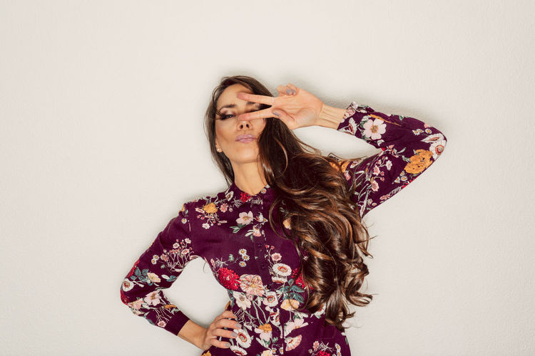 Fashionable woman gesturing peace sign against white background