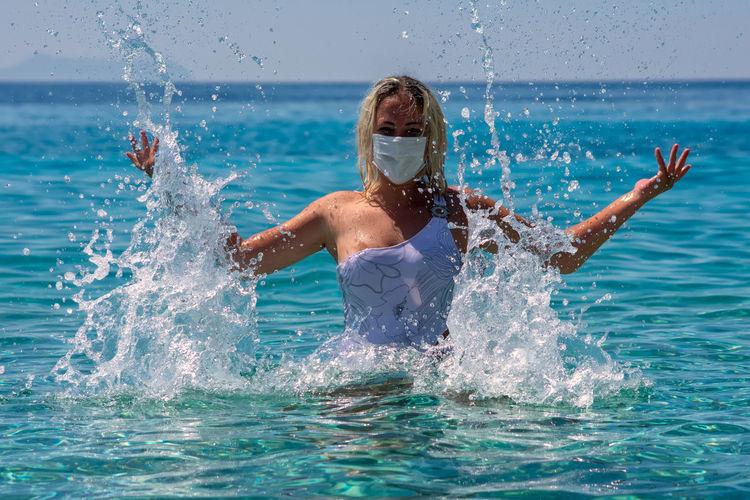 Woman wearing facemask enjoying in swimming pool against sea