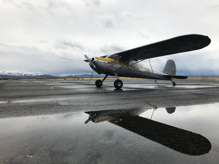 Airplane on airport runway against sky during rainy season