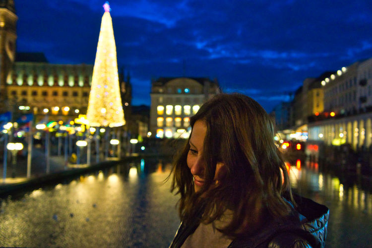 Side view of thoughtful woman looking away in illuminated city at night