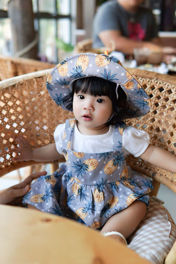 Portrait of cute baby girl sitting at restaurant