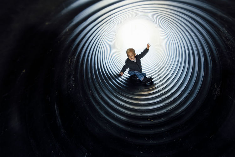 High angle view of boy standing in tunnel