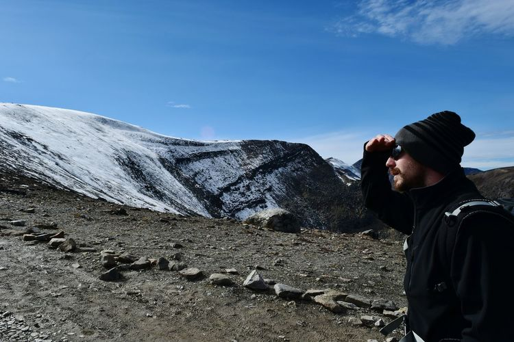 Side view of male hiker shielding eyes at mountain against blue sky on sunny day