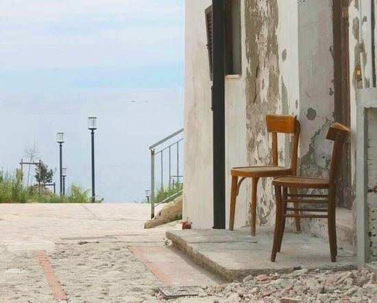Solitudine. Water Sea Horizon Over Water Street Light Empty Building Exterior Solitude Day Tranquility Remote Sky Tranquil Scene Outdoors Park Bench Nature Footpath Shore No People Scenics Ocean Chairs Old