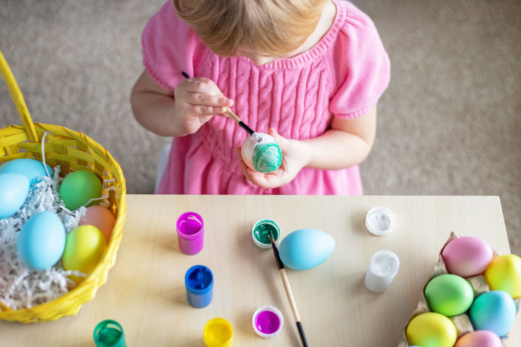 Little girl in easter bunny ears painting colored eggs. eastercelebration at home and craft concept.