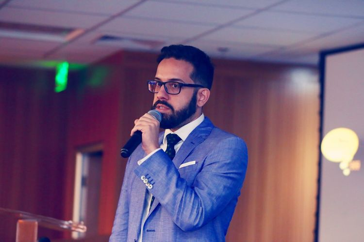 Confident businessman speaking in microphone during event