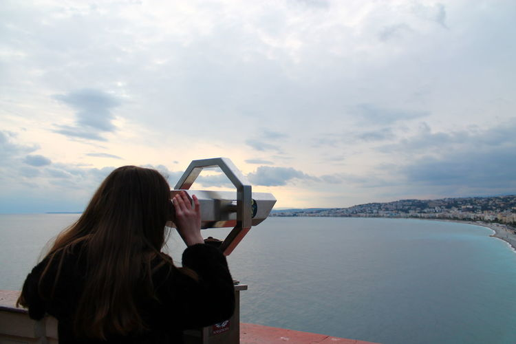 Rear view of woman looking through telescope against sea and sky