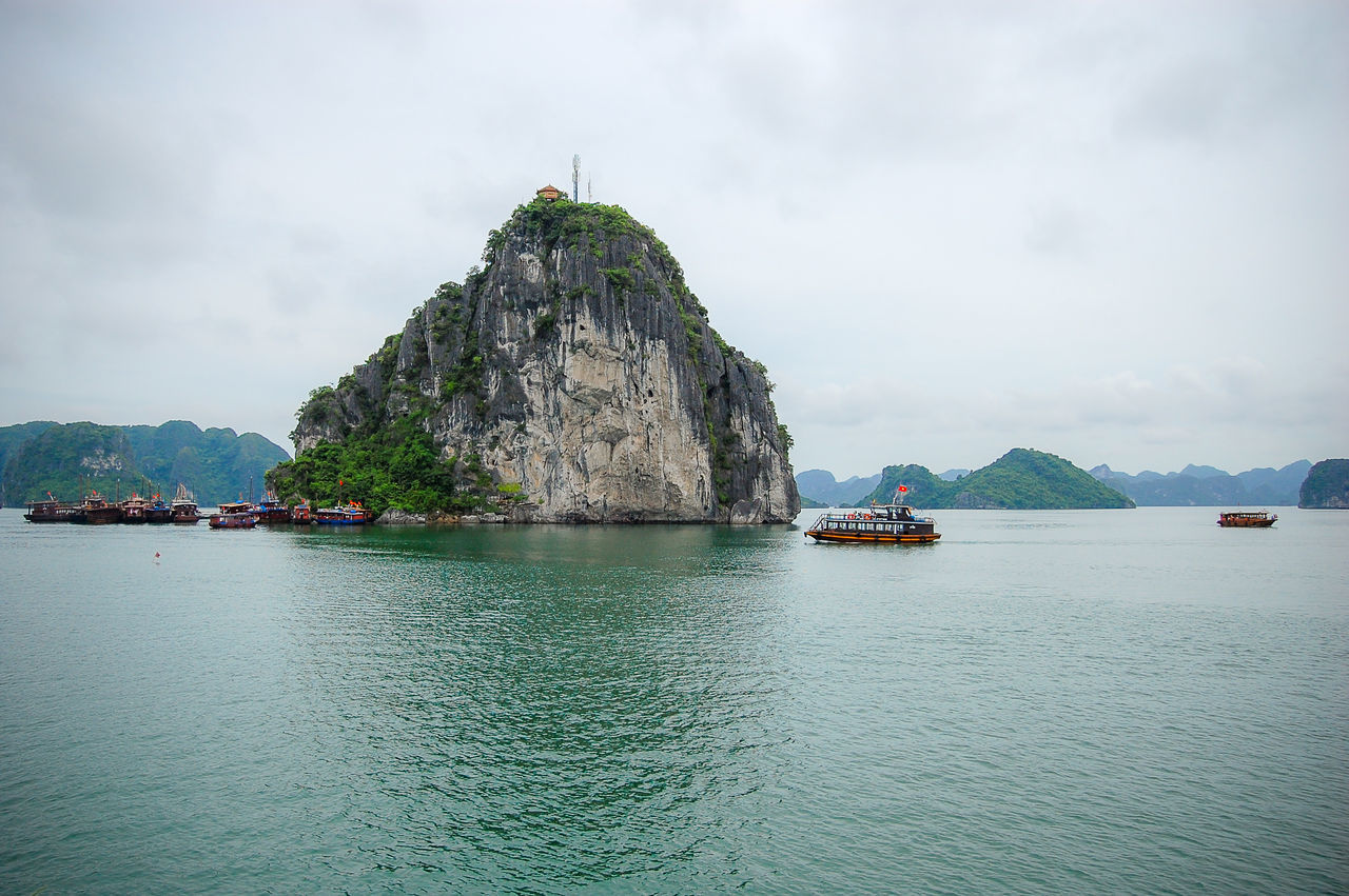 Boats Sailing On Water By Rock Formation Against Sky At Halong Bay