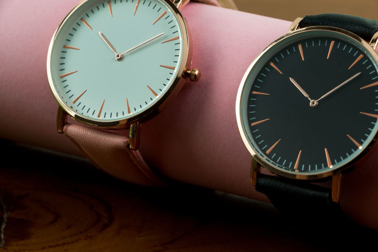Close-up of wristwatches on pink rolled paper at table