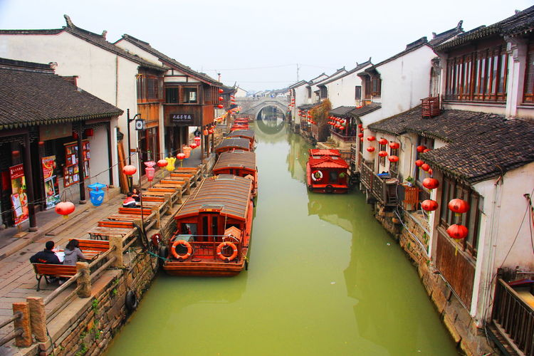 High angle view of houseboats moored on canal amidst houses