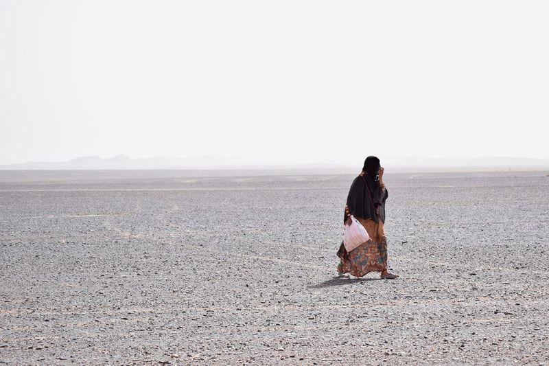 Woman walking at desert against sky