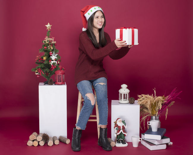 Smiling Woman Holding Gift While Sitting Against Red Background During Christmas