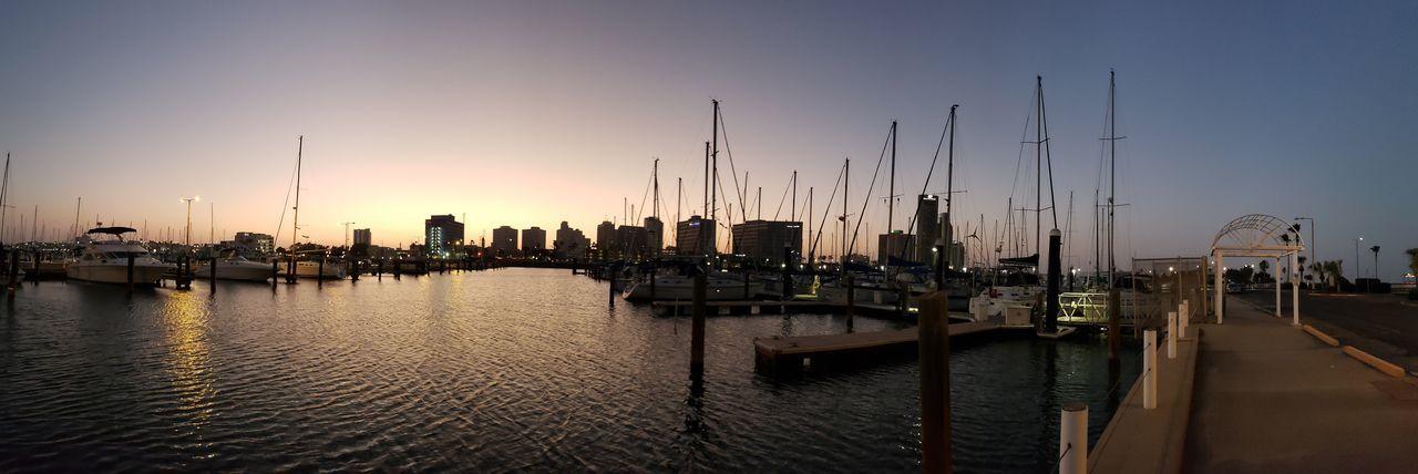 Sailboats in city at sunset