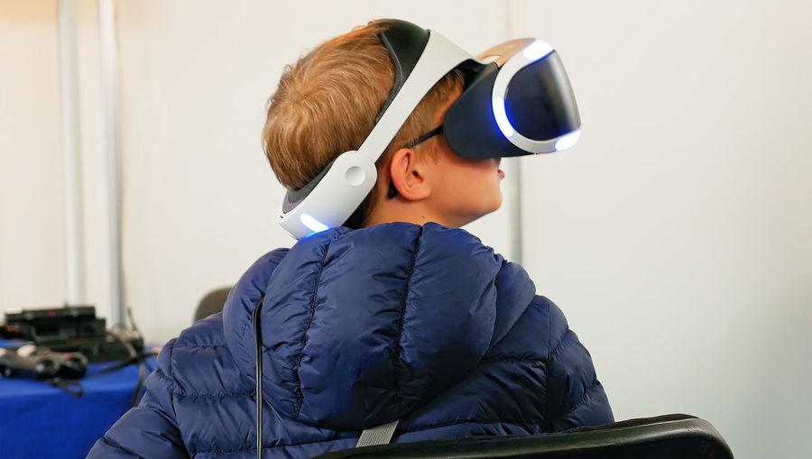 Rear view of boy using virtual reality simulator