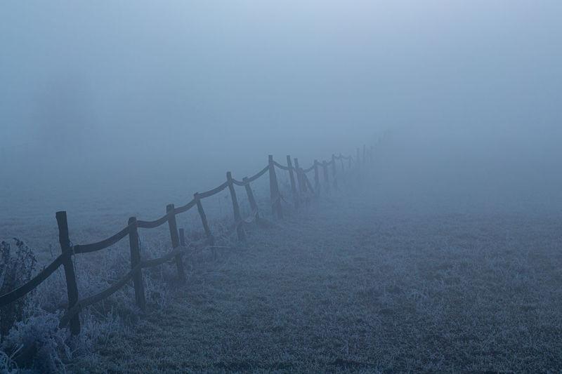 Fence on land against sky