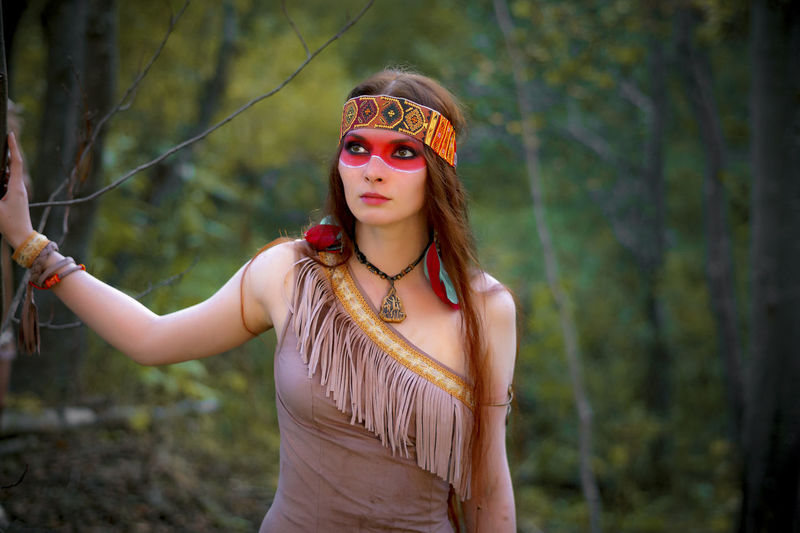 Young Woman In Traditional Clothing Looking Away While Standing In Forest