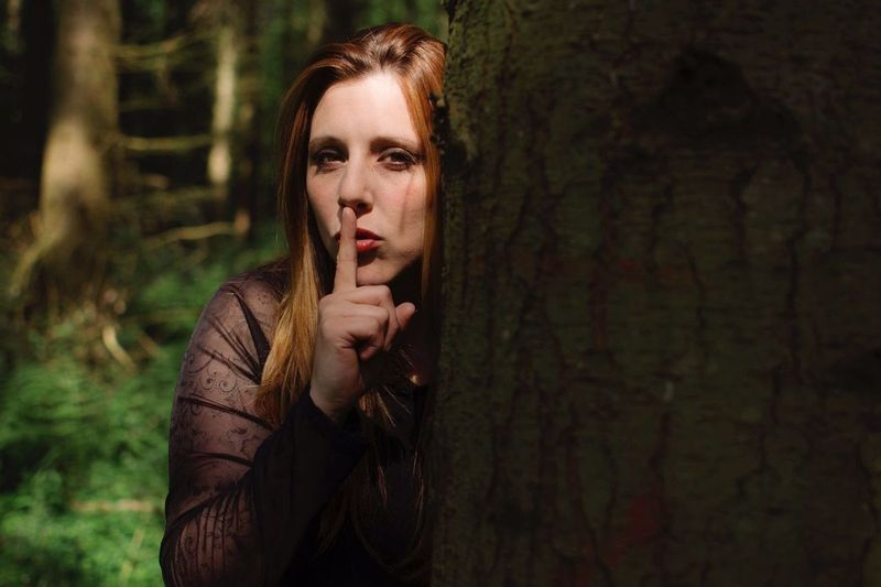 Portrait of young woman with finger on lips standing by tree in forest