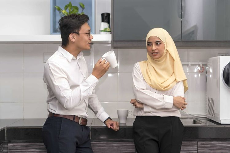Two young executive malay having a break at pantry Two People Three Quarter Length Young Adult Front View Young Men Standing Real People Adult Young Women Business Men Business Person Occupation Males  Indoors  Holding Office People Women Businessman Coworker