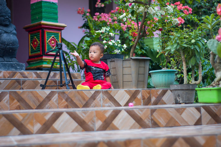 Full length of cute baby girl sitting on potted plant