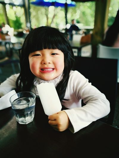 Portrait Of Cute Girl Having Popsicle Stick At Table In Restaurant