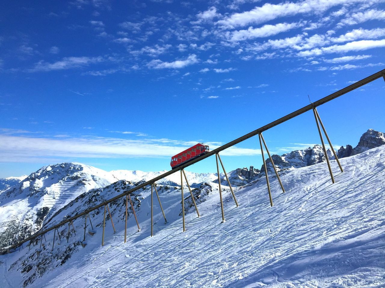 snow, cold temperature, winter, weather, nature, sky, day, beauty in nature, white color, outdoors, railing, cloud - sky, mountain, frozen, scenics, blue, tranquil scene, snowcapped mountain, low angle view, mountain range, no people, landscape, tree, ski lift