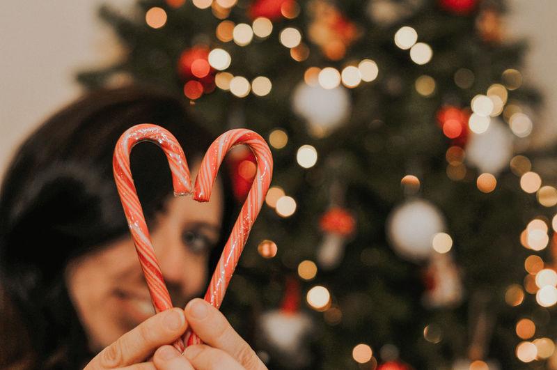 Close-up of hand holding illuminated christmas tree