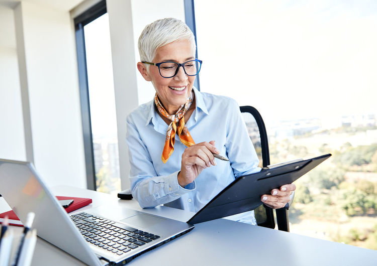 Smiling businesswoman working while sitting at table