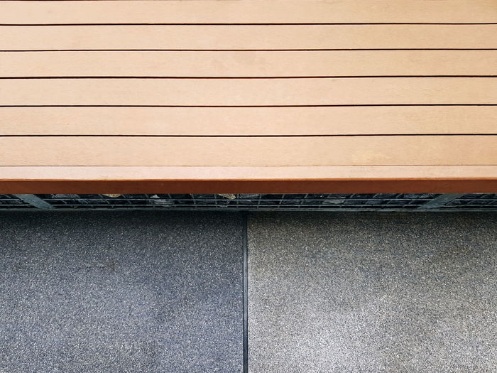 High angle view of wooden plank bench by the street