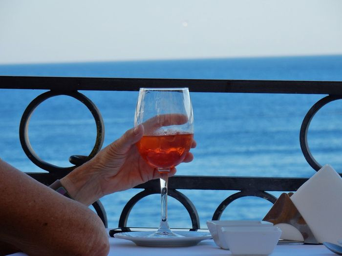 Close-up of hand holding drink in glass on table against sea and sky