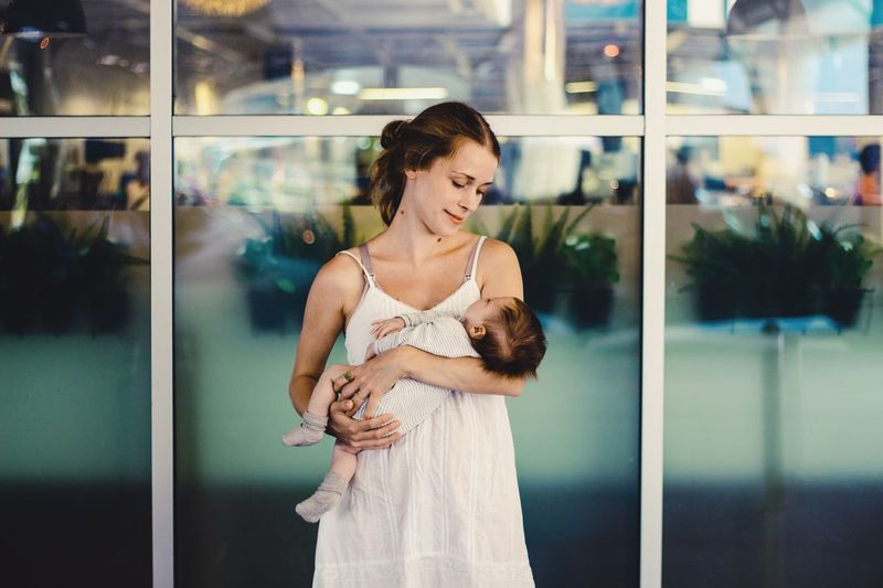 happy mother carrying her sleeping baby Caucasian Mother Motherhood Baby Holding Carrying Women Young Adult Adult Standing One Person Glass - Material A New Beginning Reflection Real People Young Women Beauty Beautiful Woman Three Quarter Length Fashion Window Hairstyle Contemplation