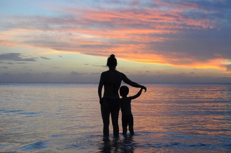 Rear View Of Silhouette Of Mother And Son On Beach Against Sunset Sky