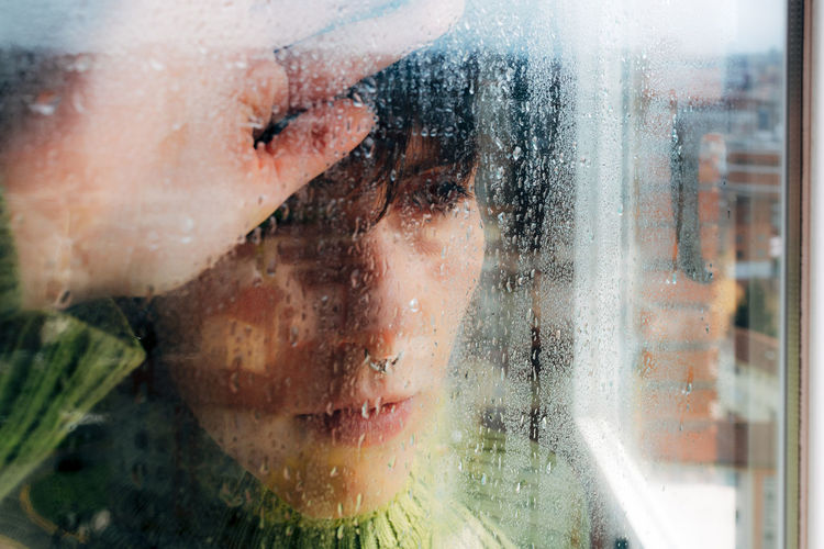 Portrait of wet boy looking through window