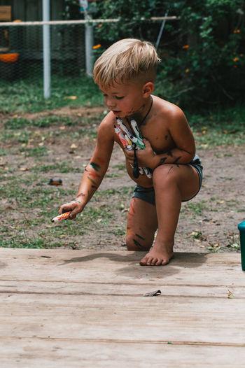Full length of shirtless boy coloring on wood.