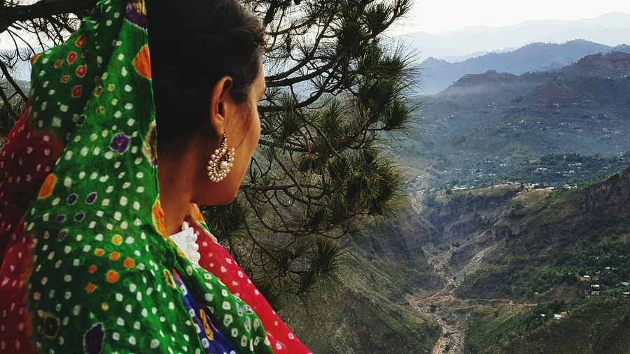 Woman in traditional clothing overlooking landscape