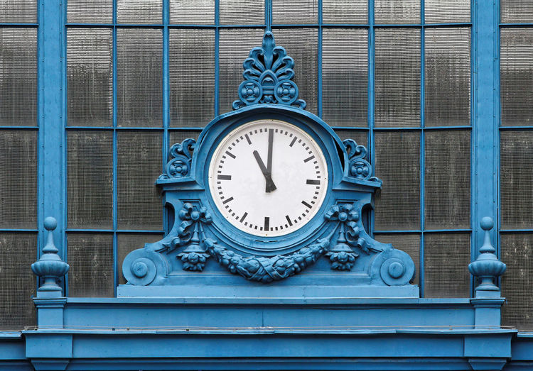Close-up of blue clock against window