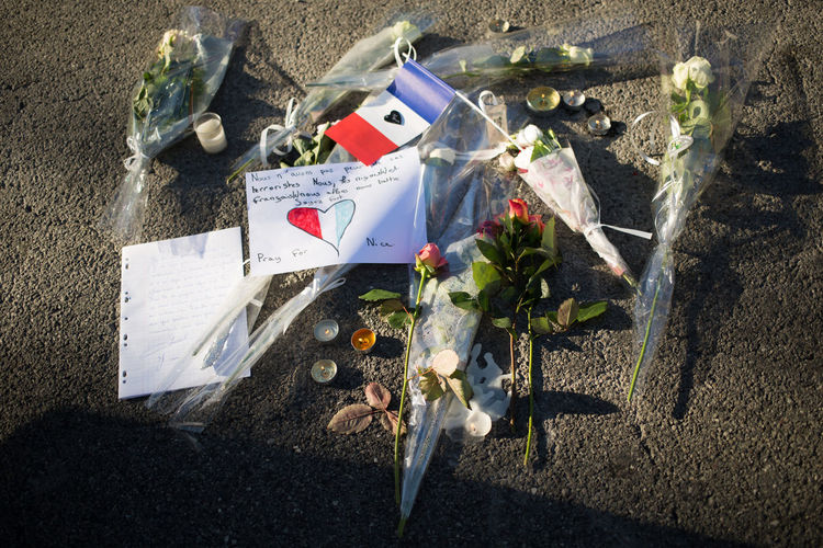 High angle view of french flag with bouquets on road after terrorist attack