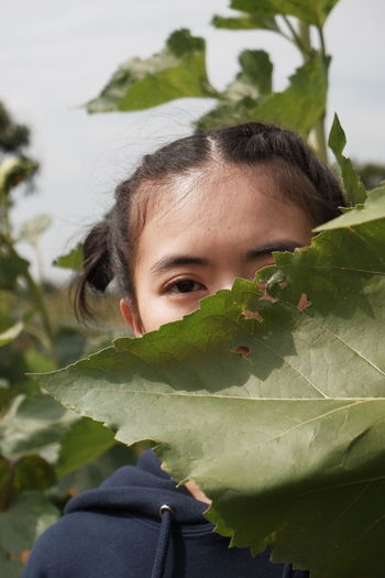 Close-up portrait of young woman by leaves outdoors