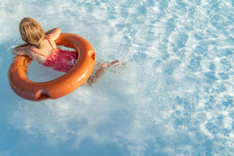 High angle view of girl floating in swimming pool