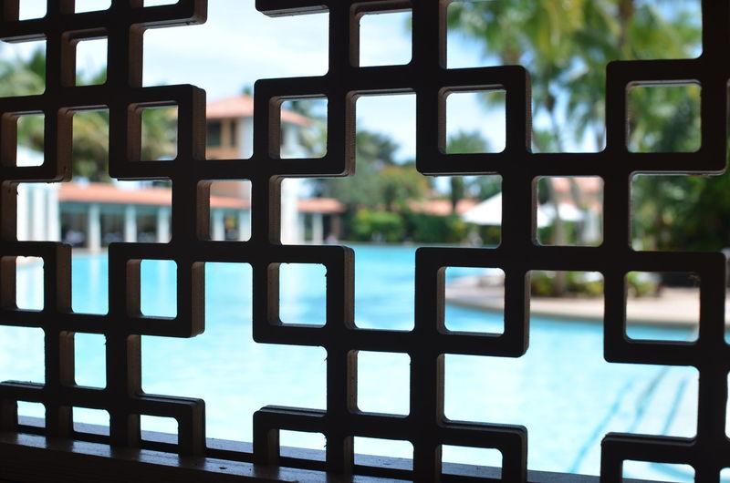 Swimming pool seen through metal grate